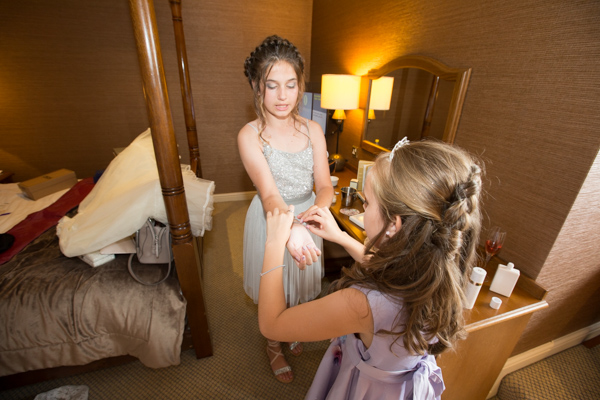 Bridesmaids helping each other fasten jewelry