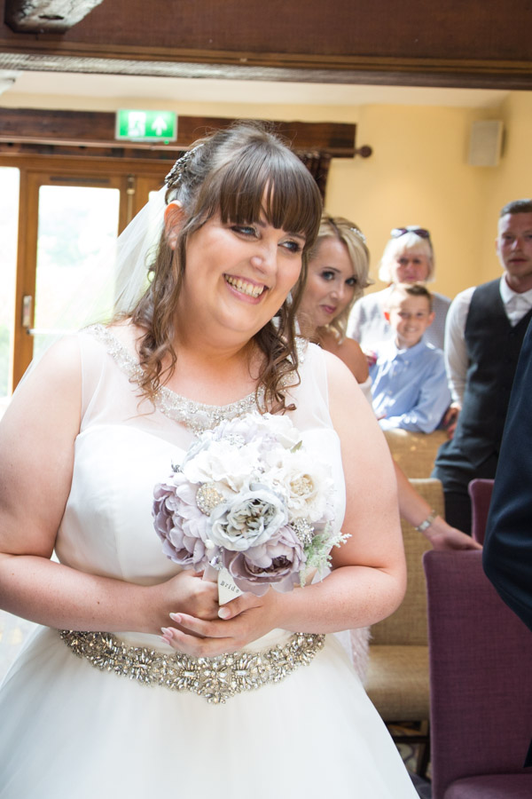 Bride smiling at the bottom of the aisle at Tankerlsey Manor Wedding