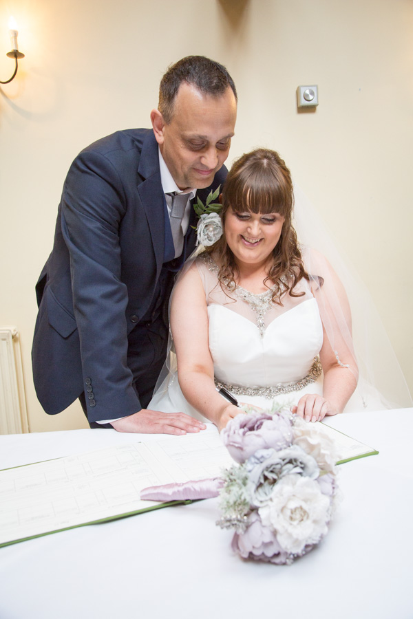 Bride and Groom signing the register at Tankersley Manor Wedding