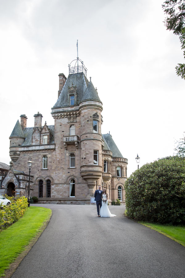 bride and groom standing outside Cornhill Castle Scotland