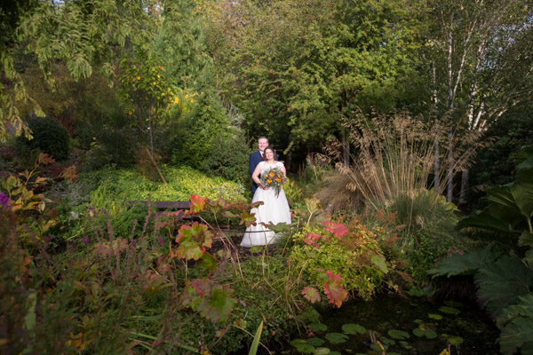 Bride and Groom standing in the gardens of Horselygate Hall surrounded by flowers Wedding Photographer Barnsley
