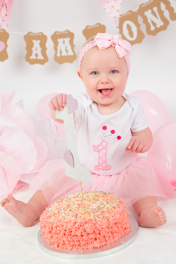 baby girl in pink tutu and one year old costume at cake smash barnsley