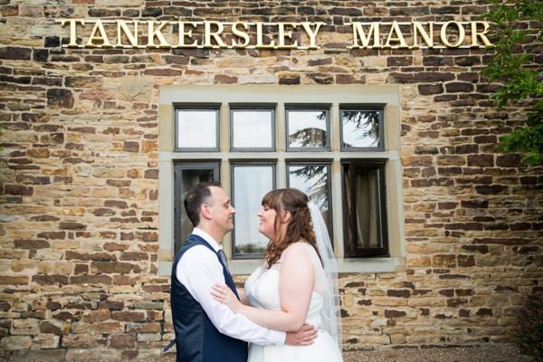 Bride and Groom standing next to Tankersley Manor sign at their Tankersley Manor Wedding day Wedding Photographer Barnsley