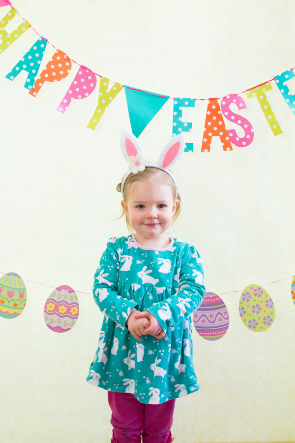Girl in blue top wearing bunny rabbit ears with a hapy easter sign behind her