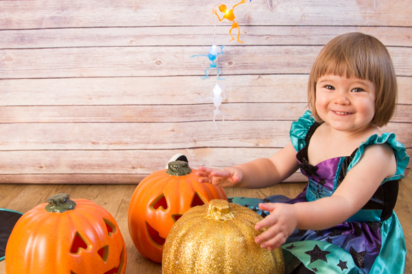 Girl sitting with pumpkins during a Halloween Themed photo shoot