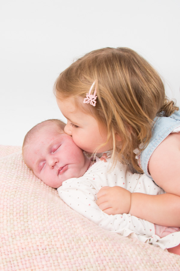 Toddler kissing a baby's cheek at Barnsley family photography session