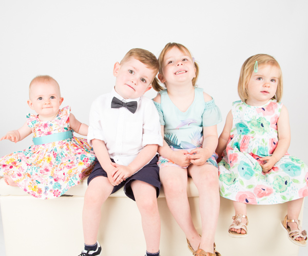 Children sitting on a bench and smiling during Barnsley Studio Photography Session