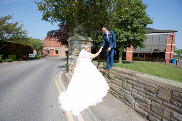 Groom helping Bride over the wall at Burntwood Court Hotel Wedding Wedding Photographer Barnsley