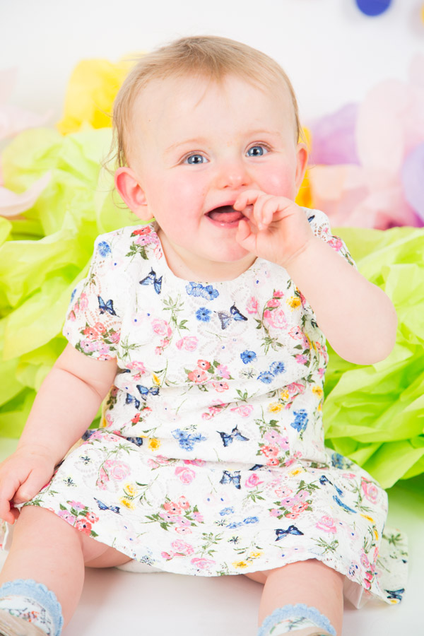 baby smiling against a colourful backdrop for first birthday shoot