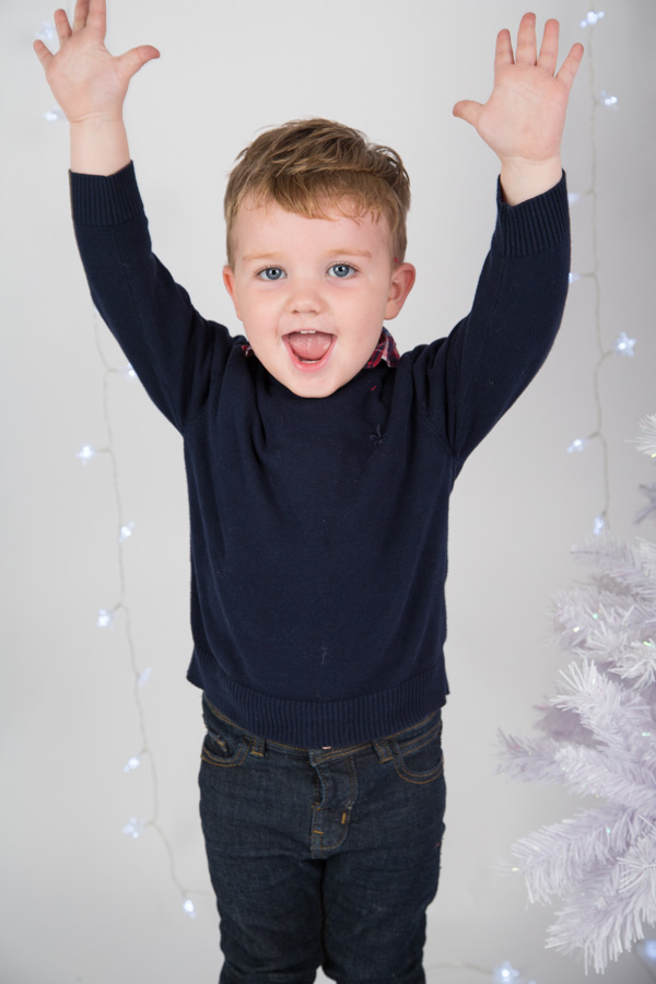 boy with his hands in the air next to a Christmas tree