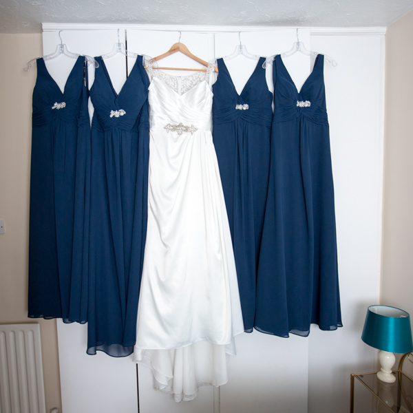 Bridal Gown and Bridesmaid Dresses hanging on a wardrobe
