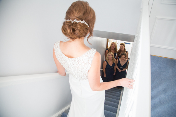 Bridesmaids looking at the bride as she walks down stairs