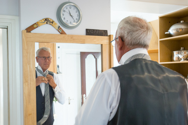 Father of the Bride doing his tie in the mirror