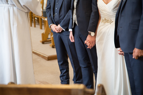 Bride and groom holding hands at All Saints Church Pontefract Wedding