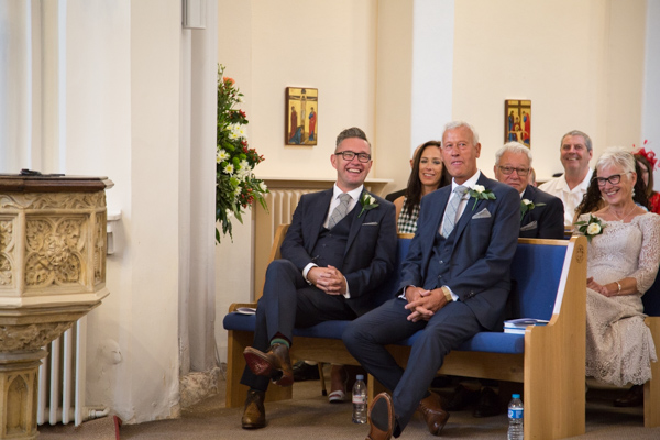 Wedding guests laughing in All Saints Church Wedding