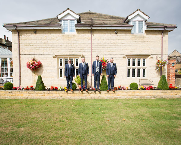 Groom and Groomsmen standing on the wall at Rogerthorpe Manor wedding Wedding