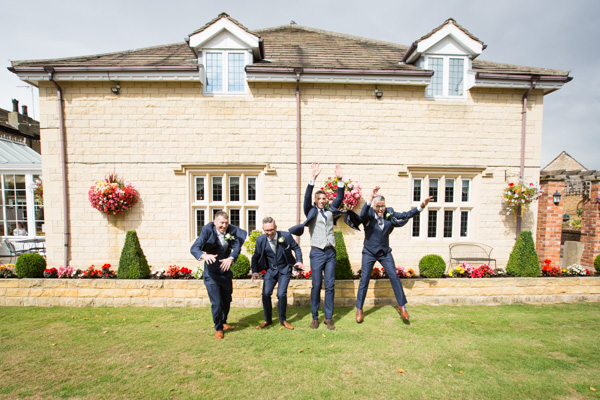 Groom and Groomsmen jumping off wall at Rogerthorpe Manor Wedding