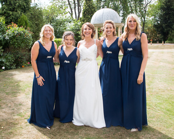 Bride and Bridesmaids laughing in the grounds of Rogerthorpe Manor
