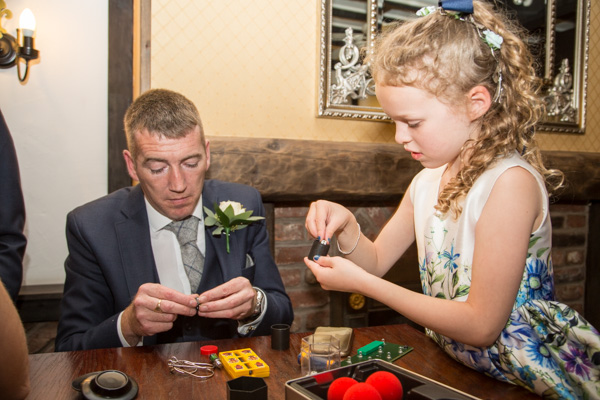 Wedding guests doing magic tricks at Rogerthorpe Manor Wedding