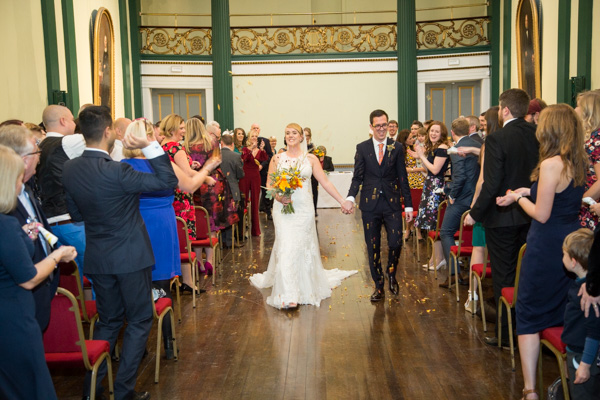 Bride and Groom walking down the aisle through confetti at Cutler's Hall Wedding Sheffield