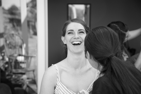 Bride laughing while having her makeup done