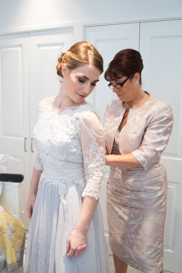 Mother of the Bride fastening bridal gown
