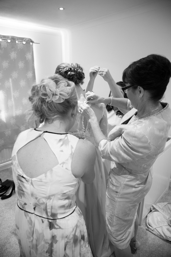 Bridal party helping bride into her wedding dress