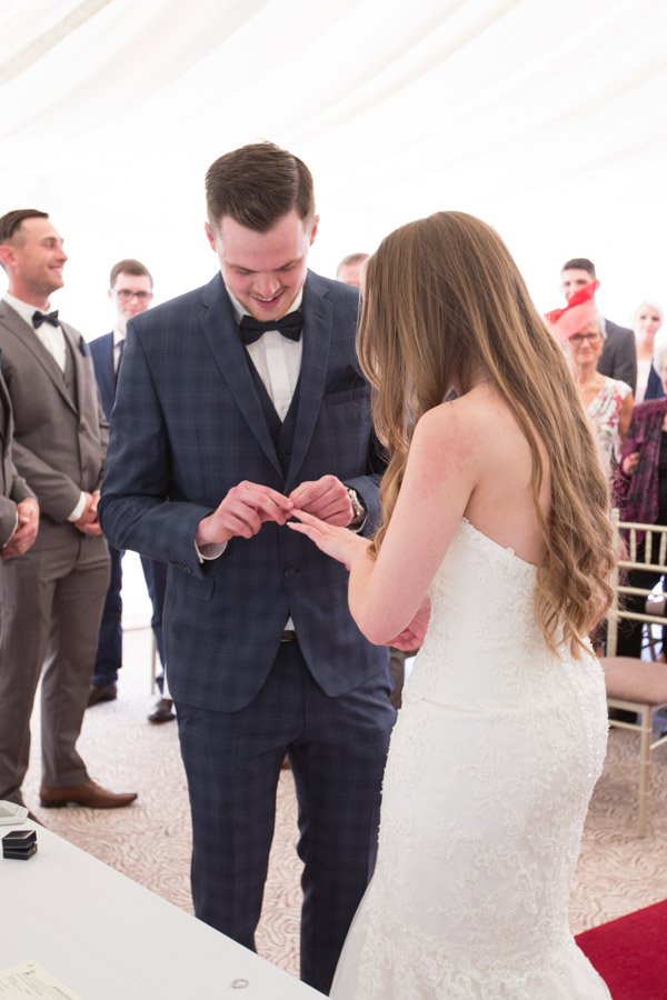 Groom bride exchanging rings during wedding ceremony