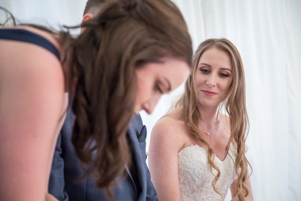 Bride watching her sister sign the register as her witness