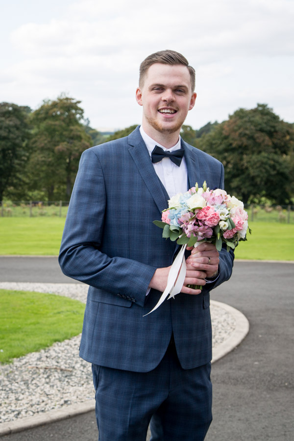 Groom holding the bridal bouquet at Cornhill Castle