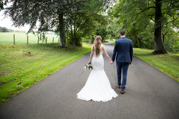 Bride and Groom holding hands and walking in the grounds of Cornhill Castle on their wedding day
