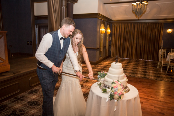 Bride and Groom cutting their cake with a sword