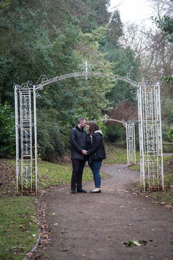 Couple standing under the white arch in the rose walk at Locke park
