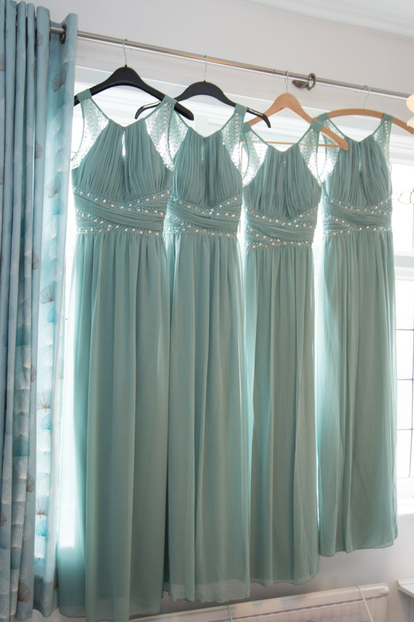 Green bridesmaid dresses hanging on a window with beaded detail from Dorothy Perkins