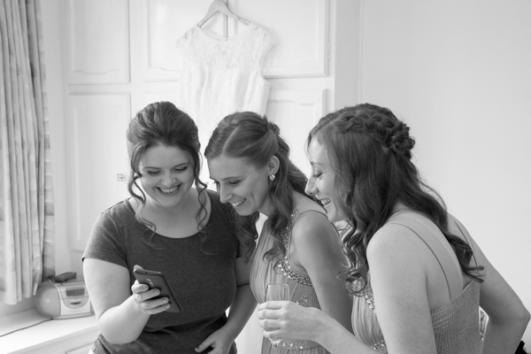 Bridal party laughing with wedding dress hanging in the background