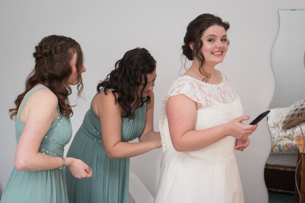 Bridesmaids fastening the bridal gown