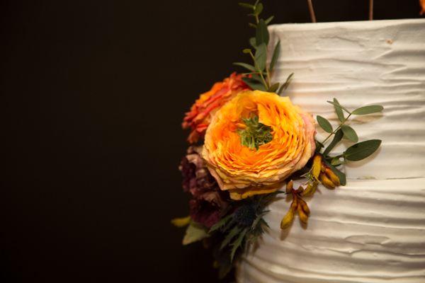 Simple wedding cake by SJ cakes with white icing and orange flower detail