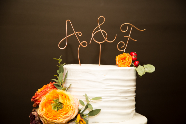 Simple wedding cake by SJ cakes with white icing and orange flower detail and initial cake topper