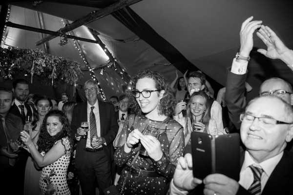 Guests cheering during cake cutting at Horsleygate Hall