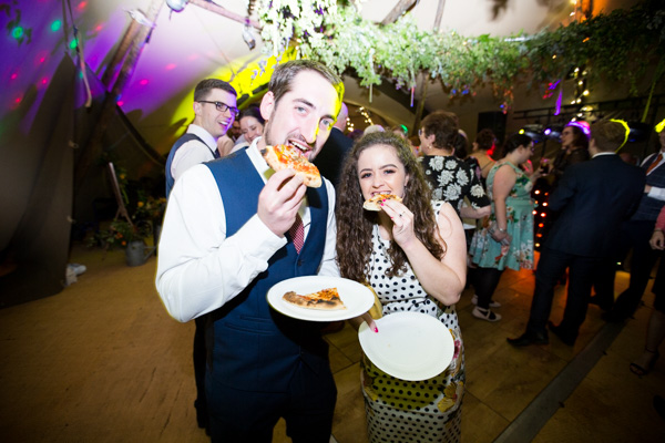Guests dancing with pizza during Horsleygate Hall wedding