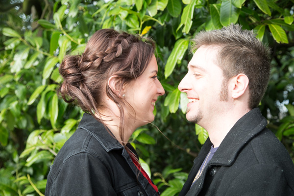 Couple looking at each other and smiling in front of a green bush in Wentworth