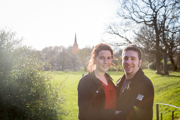 Couple standing in a faield with Wentworth Church in the background with sun glare in the image