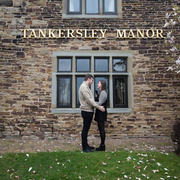 Couple looking at each other in front of Tankersley Manor sign during their pre-wedding session