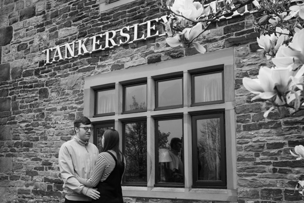 COuple in front of Tankersley Manor next to cherry blossom in black and white