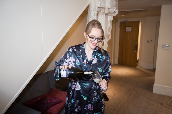 Bridesmaid in blue flowery robe pouring prosecco on the wedding morning