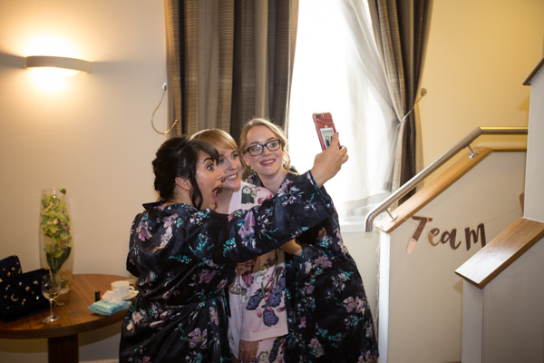 Bridesamids and bride taking a selfie on the morning of the wedding