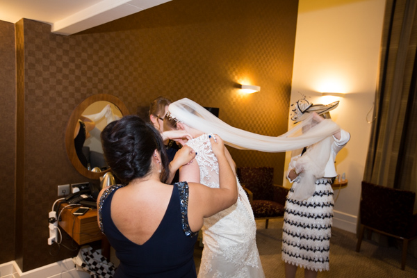 Bridesmaids and mother of the bride helping to fasten the wedding gown