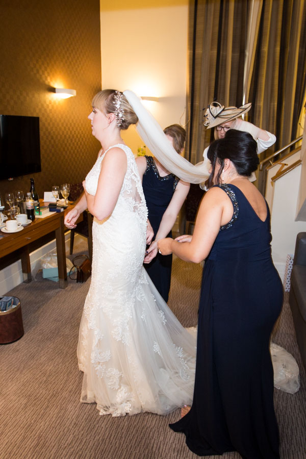 Bridesmaids and mother of the bride helping to fasten the wedding gown at Leopold Hotel Sheffield