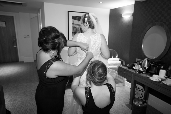 Bridesmaids fastening the wedding gown at Leopold Hotel Sheffield