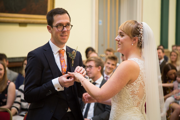 Groom placing the brides wedding ring on her finger during the ceremony at Cutlers' Hall Sheffield